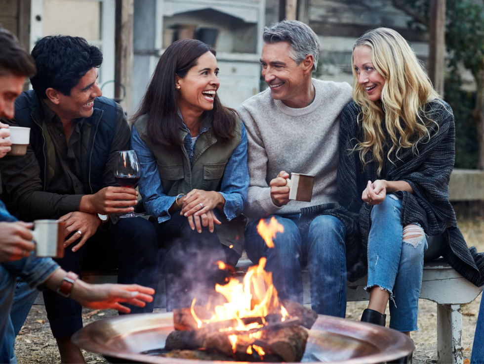 Group of happy people gathered around a fire pit on a fall day | The Canyons