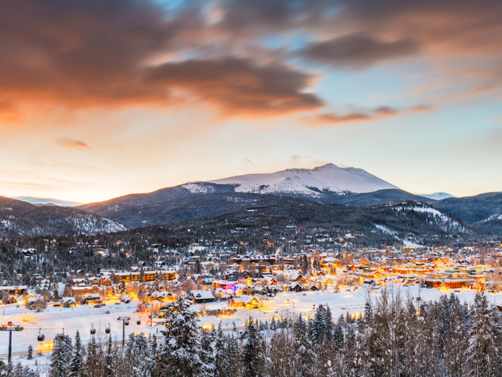 View of Breckenridge, Colorado ski town and surrounding resort at sunset against a blue and orange sky.