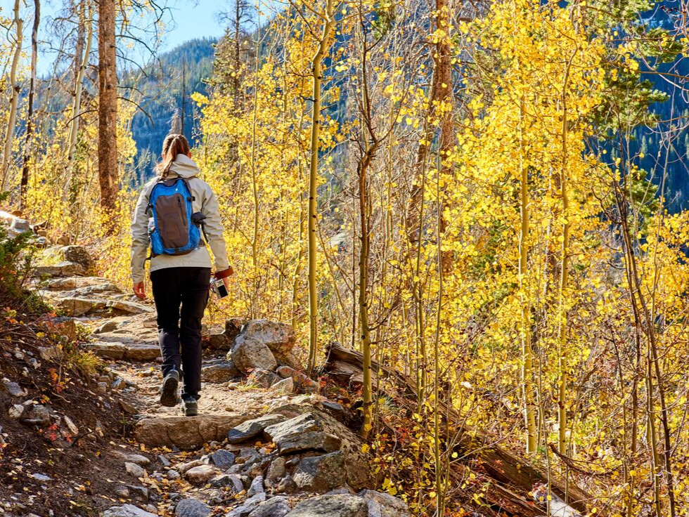 Woman hiking during the fall on a Colorado trail
