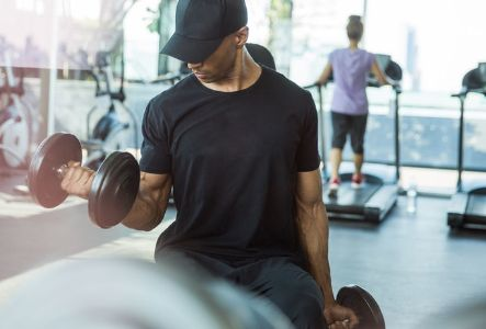 A man lifting weights at a fitness center | The Canyons | A new home community in Castle Pines, CO